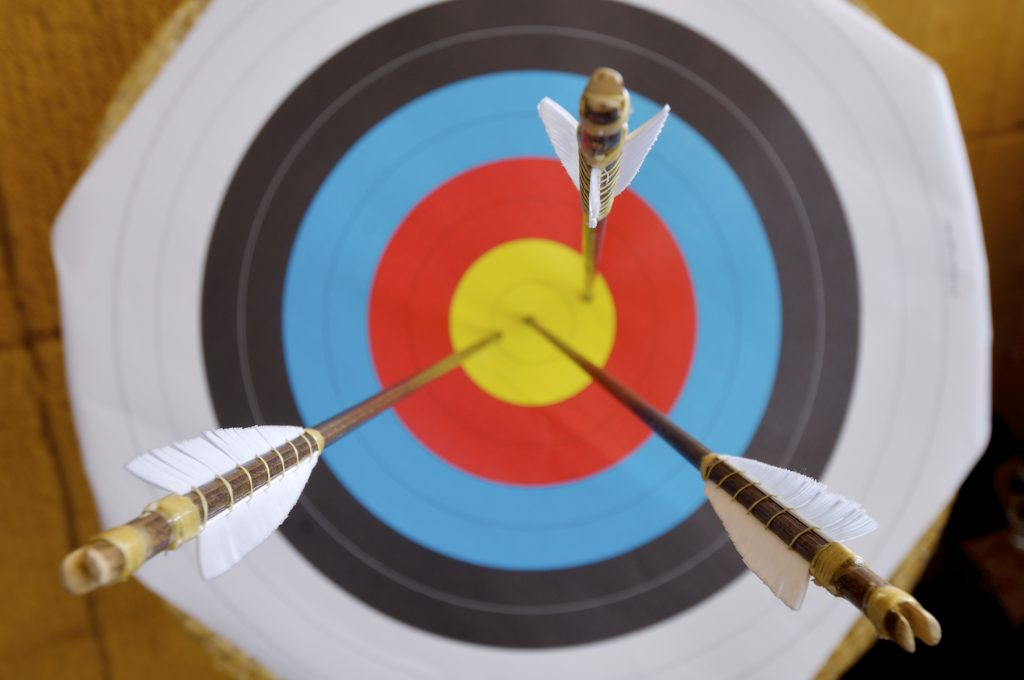Colorful target with three arrows piercing bulls eye